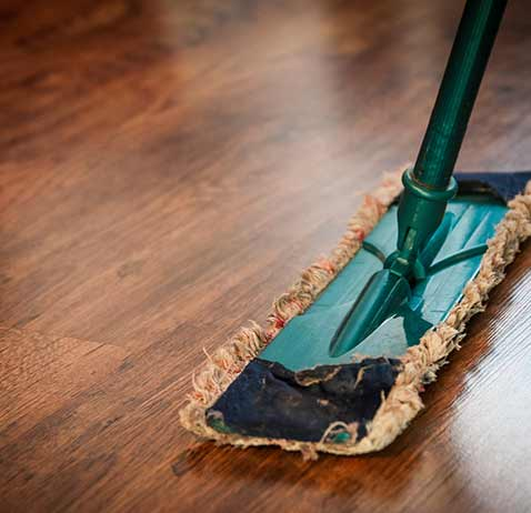 Wooden floor being cleaned with a flat mop