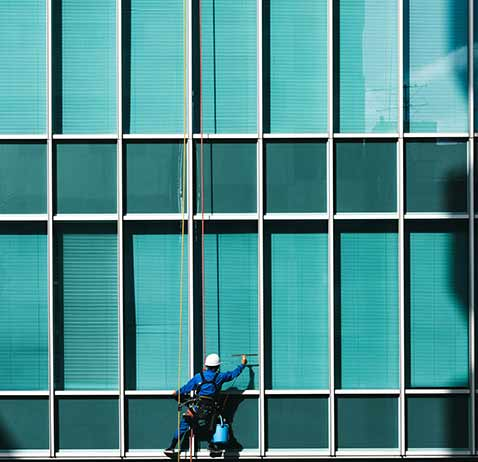 A window cleaner is suspended many levels off the ground as he works on the glass windows