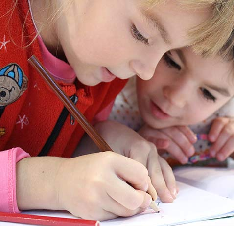 kids writing in a book together